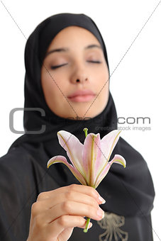 Beautiful arab woman wearing a hijab smelling a flower