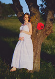Young cute pregnant woman wearing white dress in decorated garde