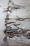 Broken pavement and pothole asphalt road after winter.