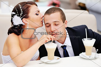 Beautiful young wedding couple  drinking cappuccino.