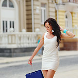 Young brunette woman with shopping bag