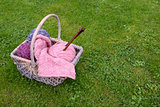 Basket of knitting, needles and wool on a lawn