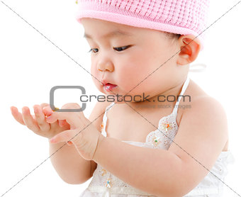 Asian baby girl eating snack