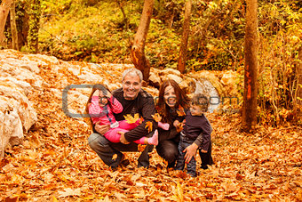 Young family in autumnal forest