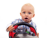 Little boy holding a toy steering wheel over white background