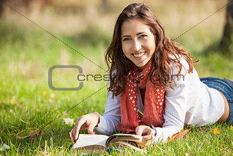 Beautiful young girl reading book while lying on grass