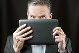 Businessman Peeks Over His Tablet