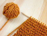 Closeup of garter stitch knitting and orange wool