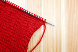 Stocking stitch in red wool on a knitting needle