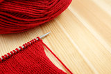 Stockinette stitch on knitting needle with red wool