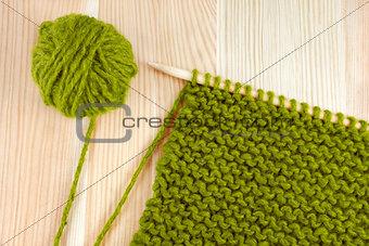 Green wool and garter stitch on knitting needle