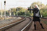Beautiful young girl is hitchhiking on railroad. Rear view