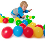 Comical child playing with colored plastic balls