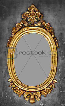 Old-fashioned gilt frame for a mirror on a concrete wall