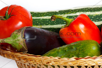 Tomato, pepper, cucumber, eggplant, squash in straw basket