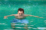 Young serious man in swimming pool