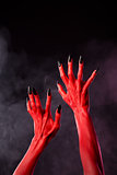 Red devil hands with black sharp nails, extreme body-art