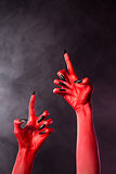 Creepy red devil hands with black nails