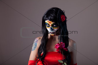 Portrait of sugar skull girl with red rose