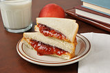 Peanut butter and jelly sandwich with school books