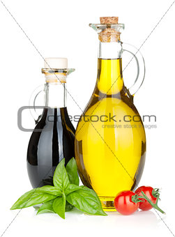 Olive oil, vinegar bottles with basil and tomatoes