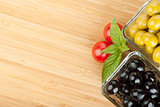 Olives, tomatoes and basil on cutting board