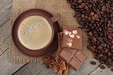 Coffee cup with spices and chocolate on wooden table texture