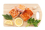 Grilled salmon with lemon slices and parsley on cutting board