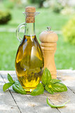 Olive oil bottle, pepper shaker and basil