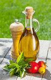 Olive oil bottle, pepper shaker, tomatoes and herbs
