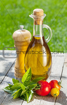 Olive oil bottle, pepper shaker, tomatoes and herbs