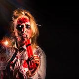 Evil female halloween zombie holding bomb