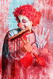 Scary hospital clown cleaning blood smeared window