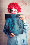 Scary clown peeking behind x-ray. Funny bones