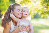 Baby hugging mother outdoors