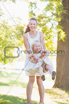 Happy mother and baby having fun outdoors
