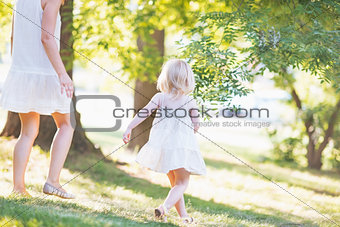 Mother and baby running in forest