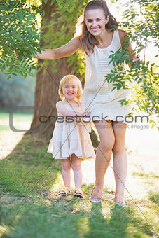 Portrait of happy mother and baby near tree