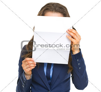 Business woman holding letter in front of face