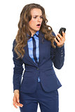 Surprised business woman looking on cell phone