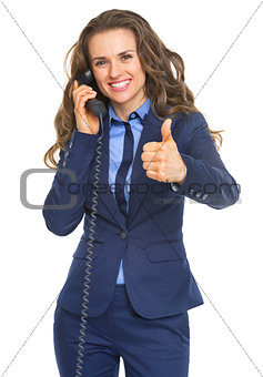 Happy business woman talking phone and showing thumbs up