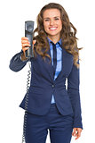 Smiling business woman giving phone handset