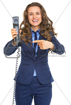 Smiling business woman pointing on phone handset