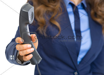 Closeup on business woman giving phone handset