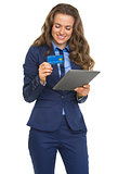 Smiling business woman with credit card using tablet pc