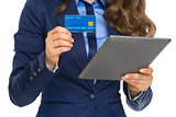 Closeup on business woman with credit card using tablet pc