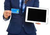 Closeup on business woman showing credit card and tablet pc blan