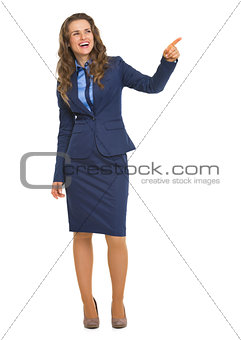 Full length portrait of smiling business woman pointing on copy