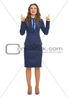 Full length portrait of smiling business woman pointing up on co