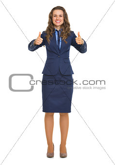 Full length portrait of smiling business woman showing thumbs up